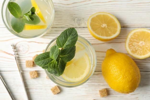 Limonade, zitronen und zuckerwürfel auf holzoberfläche