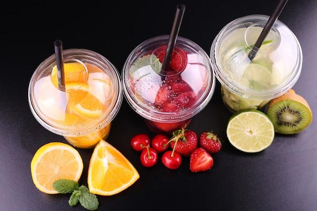 Limonade zum mitnehmen. drei tassen mit minze, kirsche, erdbeere, kiwi, limette, orage, zitrone auf schwarzraum, isoliert