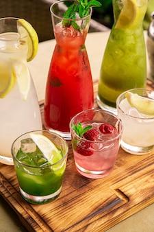 Limonaden in krügen auf dem tisch, deren zutaten hergestellt werden, sind herum angeordnet.