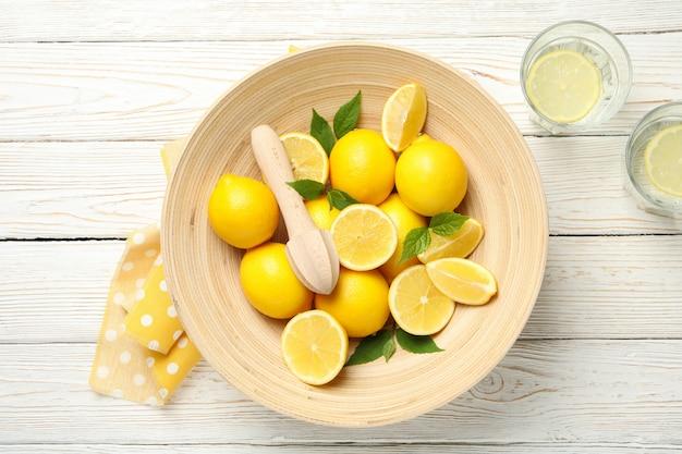 Limonaden und schüssel mit zitronen auf holzoberfläche