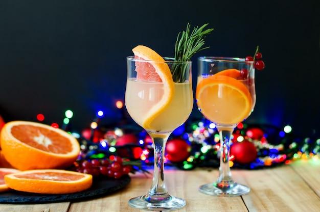 Limonadencontail mit grapefruit, orange, roter johannisbeere und rosmarinkraut.