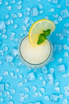 Limonadenfrappe mit runder zitronenscheibe und minze auf blauem eis.