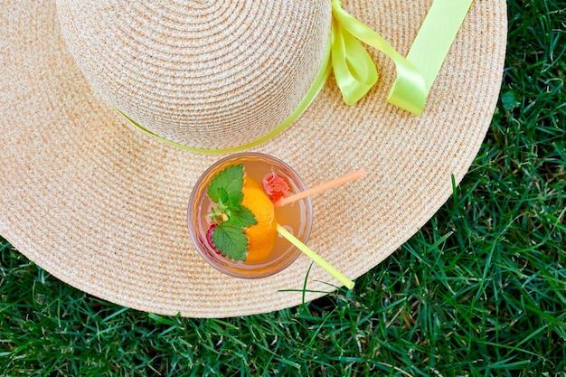 Limonadengetränk, kalter und erfrischender orangefarbener punschcocktail und strohhut im freien, helles sommerferien-lifestyle-konzept, draufsicht, kopienraum.