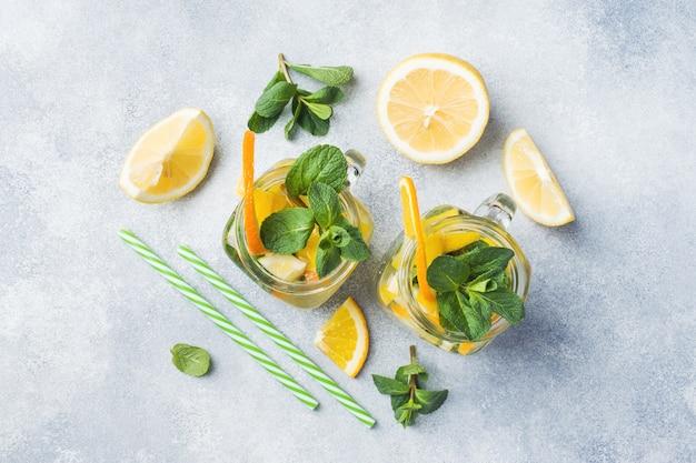 Limonadengetränk von sodawasser, zitrone und minze im glas auf hellem hintergrund.