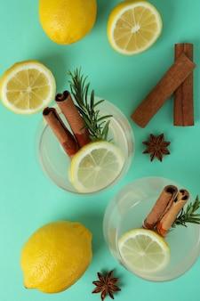 Limonadengläser mit zimt und rosmarin auf minzoberfläche