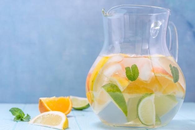 Limonadenkrug mit zitronen-, orangen- und limettenscheiben