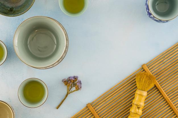 Limoniumblume mit leeren teetassen und bürste auf weißem strukturiertem hintergrund