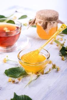 Lindenhonig in glas und schüssel mit einem honigschöpflöffel