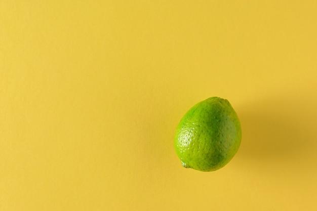 Lindgrün auf einem großen gelben hintergrund. zitrusfrüchte für die zubereitung eines getränks. flach liegen.