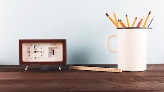 Lineal und Stifte in der Nähe von Uhr