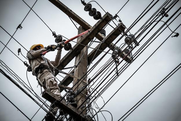 Lineman trennt das kabel mit einem klemmstab, um den beschädigten sicherungsausfall zu beheben.