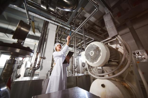 Linie der lebensmittelproduktion von raffiniertem sonnenblumenöl. arbeiterin in einer fabrik auf einer förderfläche mit flaschen pflanzenöl.