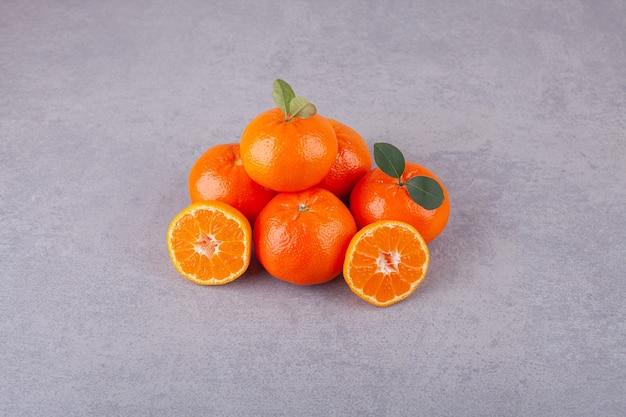 Linie der süßen mandarinenfrüchte mit blättern, die auf einen stein gelegt werden.