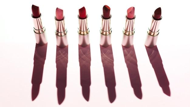Linie von metallischen lippenstiften auf rosa hintergrund
