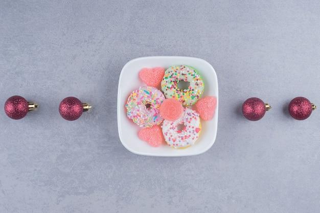 Linie von weihnachtskugeln und einer dessertplatte auf marmoroberfläche