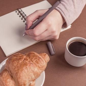Linke hand der frau mit stiftschreiben auf notizbuch an der kaffeestube. freiberufler, der in im freien arbeitet. kaffeepause mit croissant und espresso