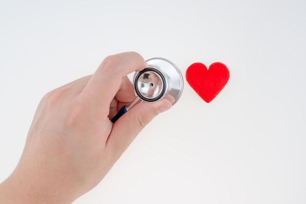 Linke hand, die stethoskop hält, um ein kleines herz mit weißem hintergrund zu messen
