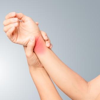 Linke hand hält das rechte handgelenk und schwellung um das gelenk