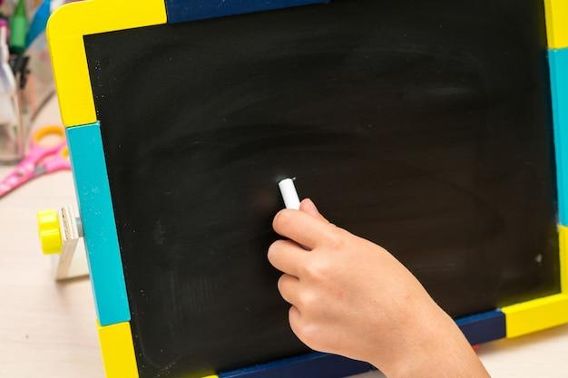 Linke hand schreiben auf schulbank auf schwarzem hintergrund