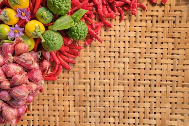 Linke seite der traditionellen thailändischen lebensmittelzutat wie trockene chilis, kleine rote zwiebeln, limette und thailändisches gemüse, layout auf einem traditionellen thailändischen holzständer-holzmuster
