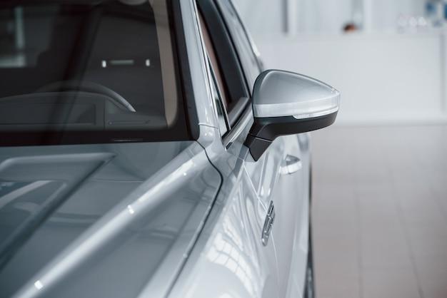Linke seite. partikelansicht des modernen weißen luxusautos, das tagsüber drinnen geparkt wird