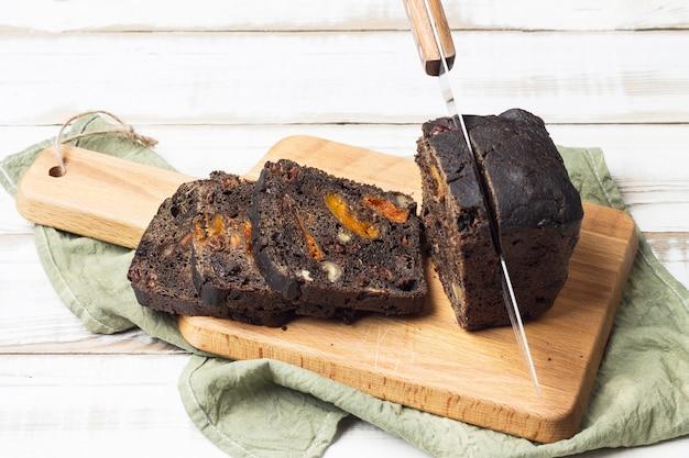 Linkes messer in einem laib schwarzbrot mit pflaumen, aprikosen und walnüssen.