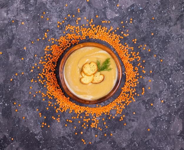 Linsen-kürbis-cremesuppe mit dill und knoblauch in einem holzteller in einem kreis von orangenlinsen