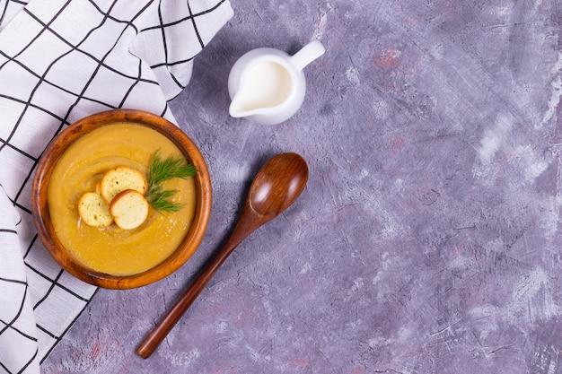 Linsen-kürbis-cremesuppe mit dill und knoblauch in einem holzteller mit holzlöffel und buttercreme