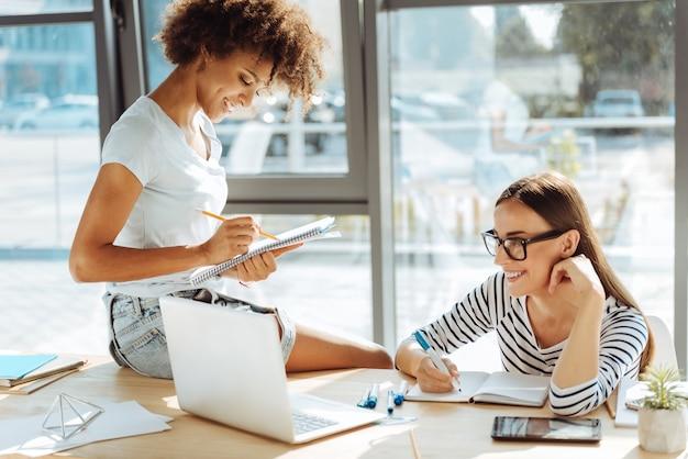 Lioke meinen job. fröhliche junge kolleginnen, die im büro sitzen und an dem projekt arbeiten, während sie laptop verwenden