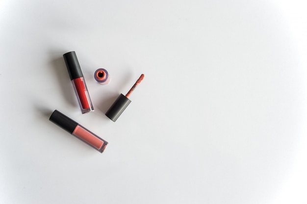 Lipgloss der roten farbe auf weißbuch mit über licht im hintergrund
