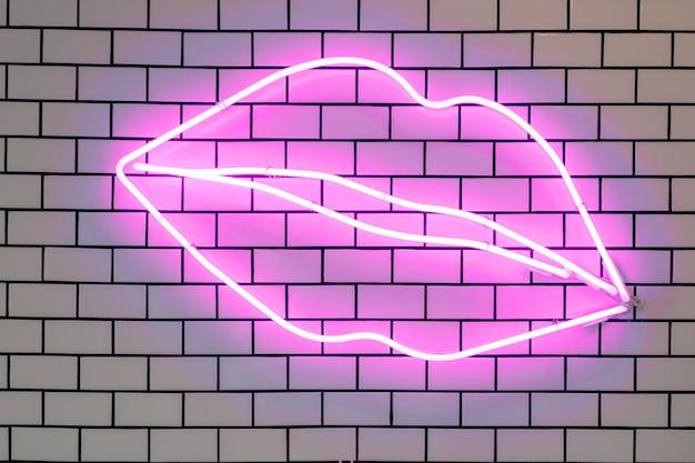 Lippenförmige leuchtreklamen führten zu dekorativen lichtern, wanddekor. lila leuchtstofflampen auf gefliester weißer backsteinmauer.