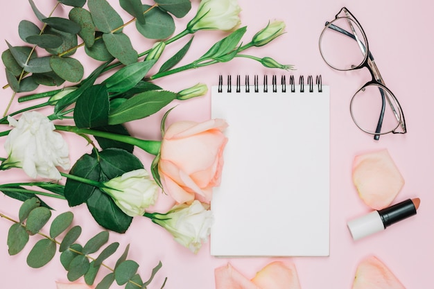 Lippenstift; brille; rosafarbener rosen- und eustomablumenblumenstrauß über rosa hintergrund