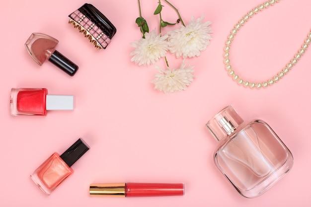 Lippenstift, flaschen mit nagellack, haarspange, blumen, perlen und parfümflasche auf rosa hintergrund. damenkosmetik und accessoires. ansicht von oben.