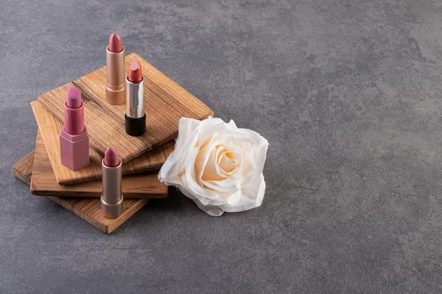 Lippenstift in natürlicher farbe in goldverpackung auf einem steintisch.