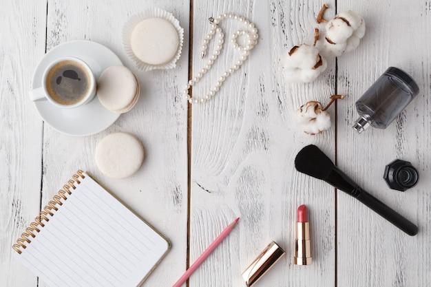 Lippenstift, make-up-pinsel und leerer papiernotizhintergrund