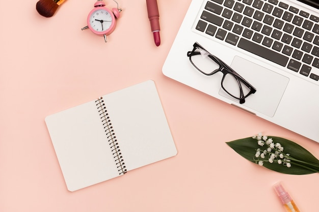 Lippenstift, make-upbürste, wecker, brillen auf laptop, gewundener notizblock auf pfirsichhintergrund