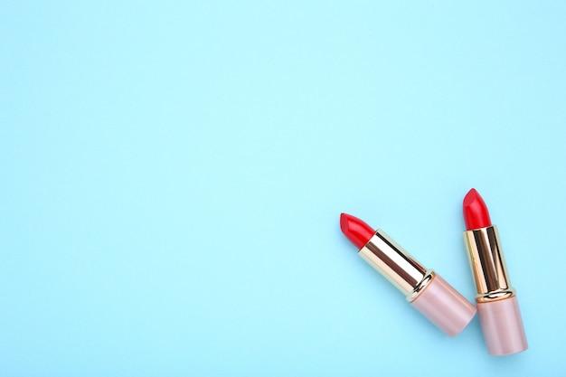 Lippenstift mit zwei rottönen auf blauem hintergrund, ebenenlage