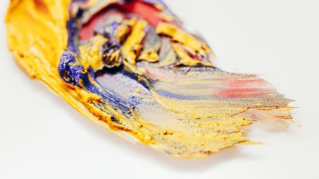 Lippenstift-mix. make-up-kunst mode. gelbe blaurote verschmierte striche auf weißem hintergrund.
