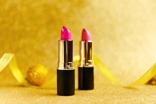 Lippenstifte auf goldenem glitzerndem hintergrund mit weihnachtsbaumspielzeug