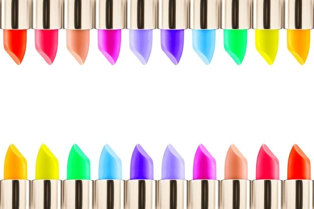 Lippenstifte bunt, einen rahmen bildend getrennt auf einem weißen hintergrund mit exemplarplatz