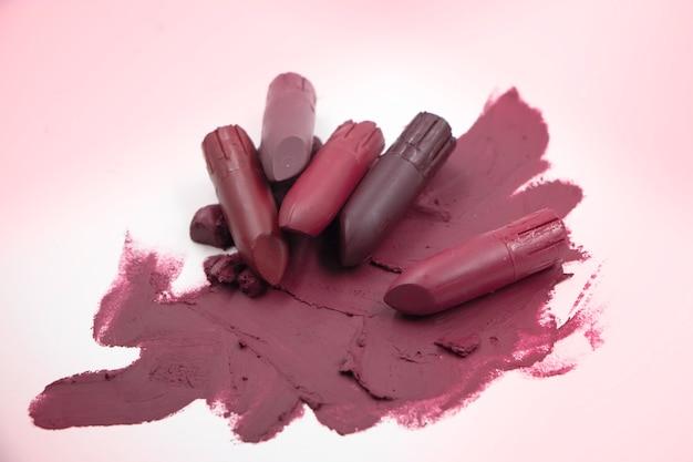 Lippenstifte setzen auf hintergrund, zeigen textur und farbe von kosmetik. verschwommenes licht herum