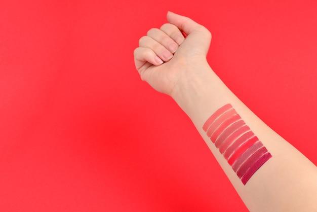 Lippenstiftmuster auf der hand der frau lokalisiert auf rotem hintergrund.