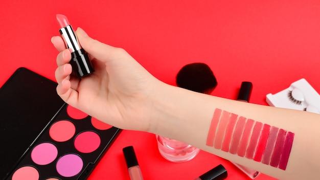 Lippenstiftmuster auf frauenhand. professionelle make-up-produkte mit kosmetischen schönheitsprodukten, foundation, lippenstift, lidschatten, wimpern, pinseln und werkzeugen.