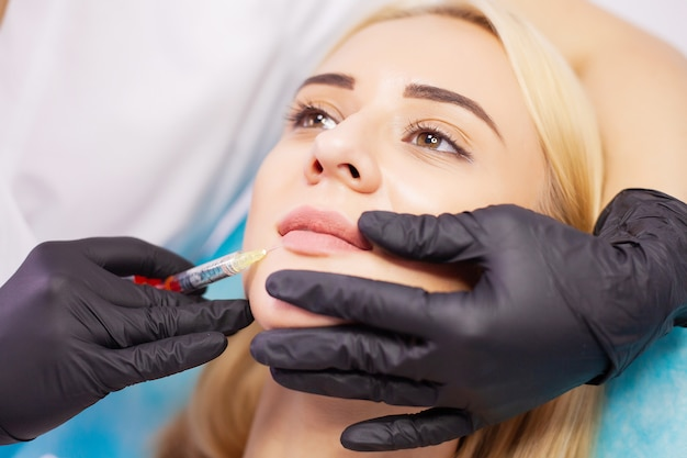 Lippenvergrößerung in cosmetology clinic. schöne frau, die schönheits-einspritzung für lippen erhält.