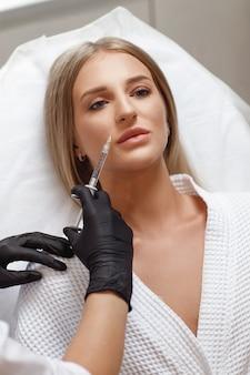 Lippenvergrößerung, lippenkorrektur. porträt weiße frau während einer operation, die gesichtsfalten füllt. plastische chirurgie. junge frau, die kosmetische injektion in lippen erhält
