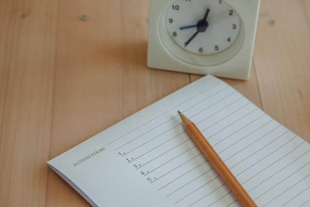Liste der aktionsgegenstände in notizbuch und bleistift schreiben