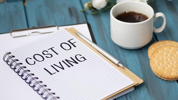 Liste der lebenshaltungskosten mit den preisen für den betrieb eines hauses auf einem holz mit kaffeetasse.
