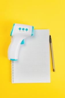 Liste der medikamente. papierheft mit stift und thermometer, draufsichtliste der pillen auf gelbem hintergrund. erkältung, grippe oder coronavirus. behandlung.