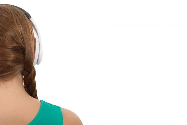 Listenning musik der jungen frau mit kopfhörer, hintere ansicht, über weiß