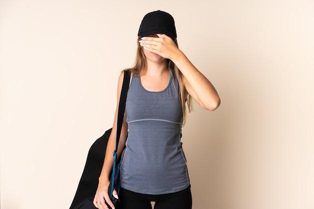 Litauische frau des jungen sports, die eine sporttasche lokalisiert auf beige bedeckte augen durch hände hält. ich will nichts sehen